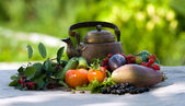 Berries, vegetables and an ancient teapot on a grey cloth — Stock Photo