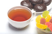 Cup with tea, a zephyr and fruit candy. — Stock Photo