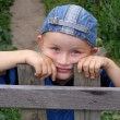 Little boy leaned against the fence — Stock Photo #1117872