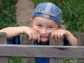 Little boy leaned against the fence — Stock Photo