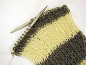 Scarf is knit by needle — Stock Photo