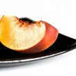 Royalty-Free Stock Photo: Red peaches slices on black dish