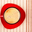 Red coffee cup on striped tablecloth — Stock Photo #1908083