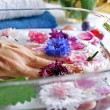 Woman elderly hand lies in a glass basin - Stock Photo