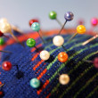 Colorful needle bed with pins - Stock Photo