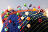 Colorful needle bed with pins — Stock Photo