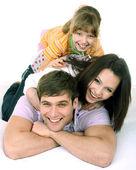 Lycklig familj på vit säng. — Stockfoto