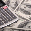 Calculator and dollars background. - Stock Photo