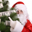 Santa Claus holding money. — Stock Photo