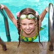 Girl in protective goggles leaves pool. — Stock Photo