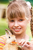 Happy girl feed rabbit with carrot. — Stock Photo