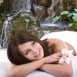 Girl in spa against waterfall. — Stock Photo