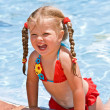 Child girl near blue swimming pool — Stockfoto