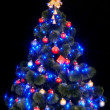 Christmas tree with light and blue star. — Foto Stock