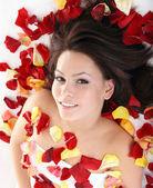 Beautiful girl in rose petal. — Stock Photo