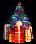 Christmas tree with flash and gift box. — Stock Photo