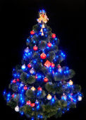 Christmas tree with light and blue star. — Stock Photo