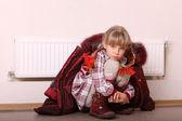 Girl in coat near radiator. Crisis. — Stock Photo