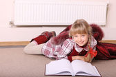 Girl lie near radiator with book. — Stock Photo