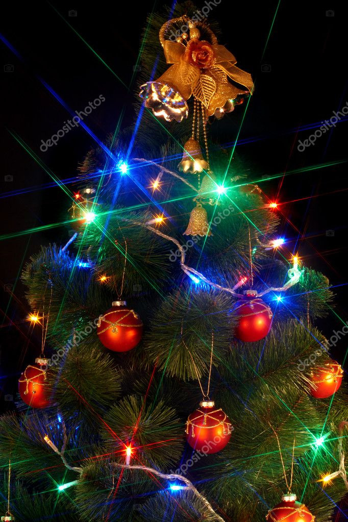 Christmas tree with flash and bell. Black background. — Stock Photo #1337401