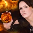 Stock Photo: Witch with fire ball on flame.