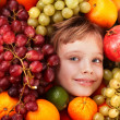 Child girl in group of fruit. — Stock Photo