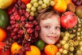 Fille enfant dans le groupe de fruits. — Photo