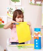 Child with scissors cut paper — Stock Photo