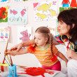 Child with teacher draw paints - Stock Photo