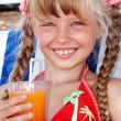 Child girl in red bikini drink juice. — Stock Photo