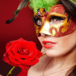 Girl with red rose and mask. — Stockfoto