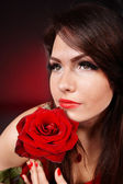 Girl with rose on red background. — Stock Photo