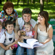 Happy family in outdoor read book — Stock Photo #2534813