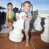 Children play chess nearly sea. — Photo