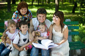 Happy family in outdoor read book — Stock Photo
