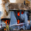 Fireman hosing down a burning house - Stock Photo