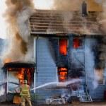 Fireman hosing down a burning house — Stock Photo