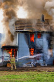 Fireman hosing down a burning house — Stock Photo