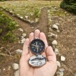 Stock Photo: Hand Held compass at Trail Junction