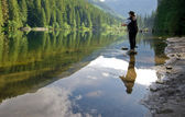 Woman fly fishing at a lake — Foto Stock