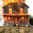 Firemen at a burning house - Stock Photo
