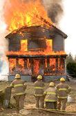 Firemen at a burning house — Stock Photo
