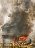Firemen at a burning house — Stock Photo
