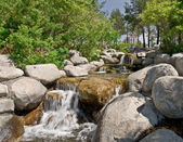 Landscaped waterfall and condominium — Stock Photo