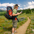 Hiker checking a GPS - Stock Photo