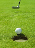 Golf ball rolling towards the hole — Stock Photo