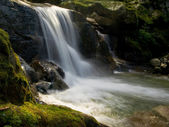 Small waterfall and mossy boulders — Stock Photo