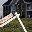 Foreclosure Sign by house - Stock Photo