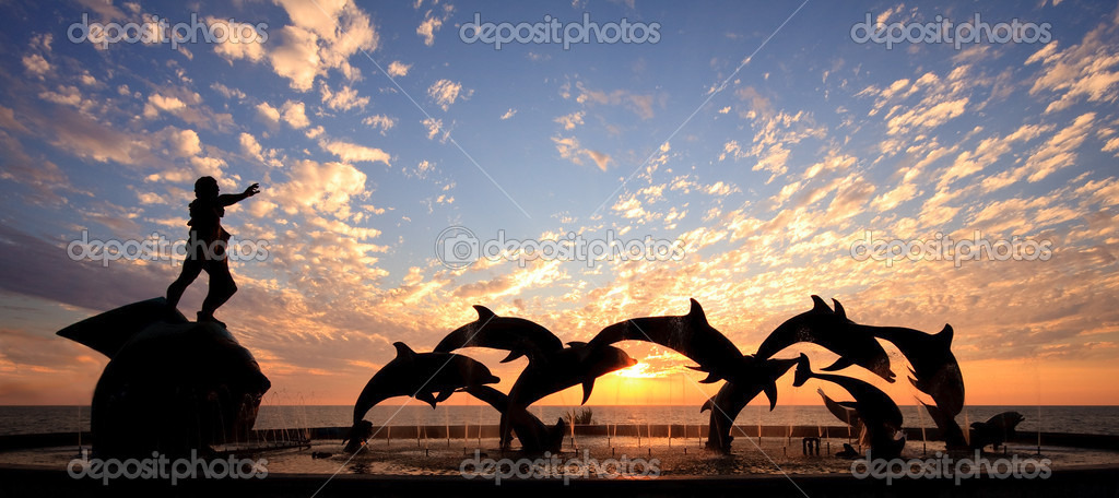 Dolphin statue in Mazatlan frames a beautiful sunset over the ocean — Stock Photo #1023181