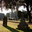 Backlit view of gravestones with church — Stock Photo